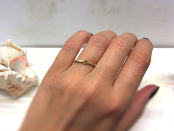 Schmaler Verlobungsring mit braunem Diamanten an der Hand