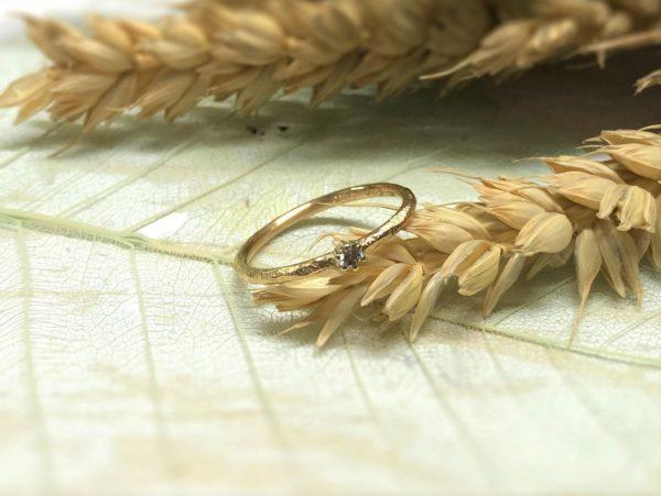 Goldverlobungsring Nellia, drappiert auf Getreide.