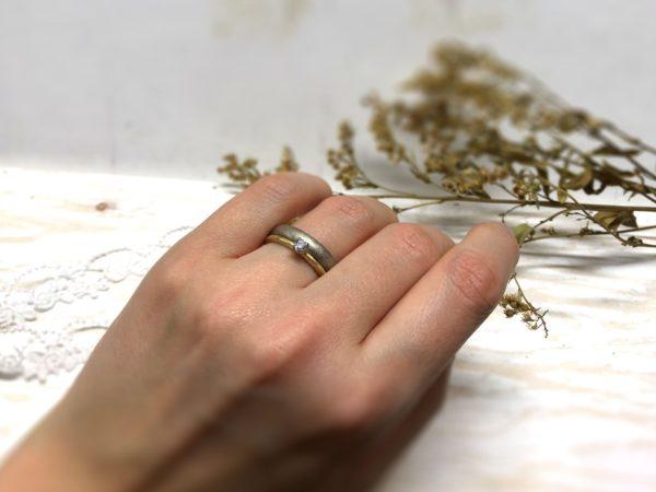 An den Trauring angesteckter Verlobungsring mit Stein.