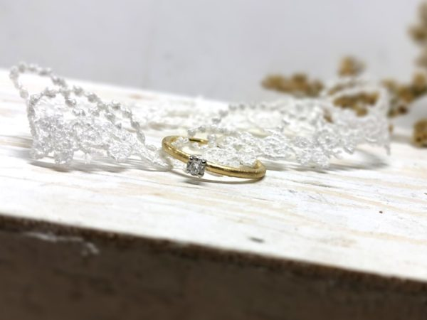 Matter und schmaler Verlobungsring mit weißem Stein in Krallenfassung.