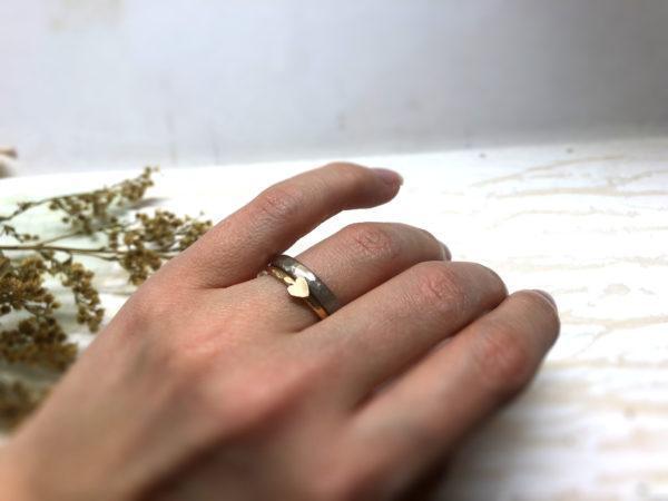 Vorsteckring mit Herzchen aus Rotgold und Gelbgold, getragen an der Hand.