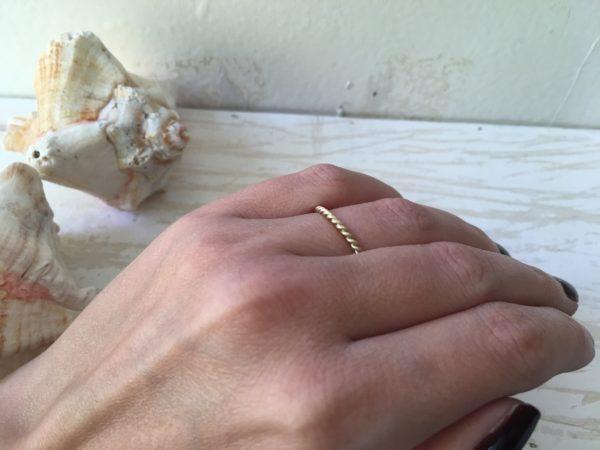 dünner kordelring an der hand aus gold