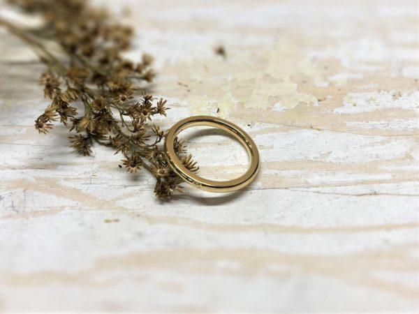 Dünner Verlobungsring aus glänzendem Gold.