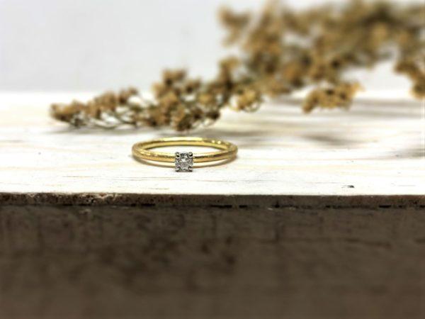 Klassischer Verlobungsring aus Gold mit Stein mit 4 Ästen gefasst.