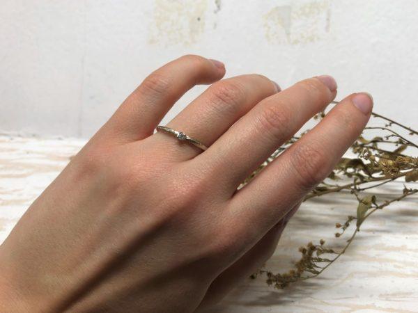 Ein schmaler, weißer Verlobungsring mit Stein, getragen an einer Hand.