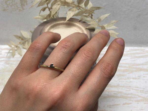 Handgemachter Herzverlobungsring namens Ellara 2, getragen an der linken Hand.