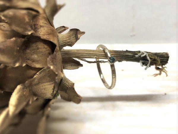 Gemusterter Verlobungsring mit blauem Stein, Modell Marenia, dekoriert auf Holz.