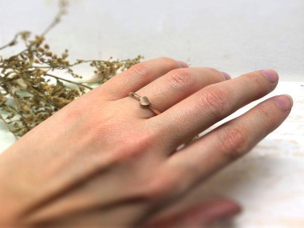 Roter Verlobungsring mit Herz an der Hand getragen.