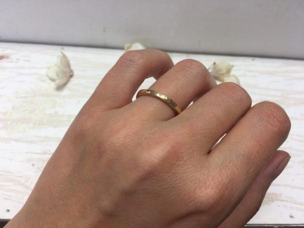 goldverlobungsring mit hammerschlag schmal an der hand