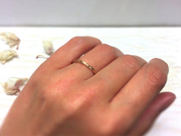 Schmaler, gedrehter Möbiusring aus Rotgold an der Hand