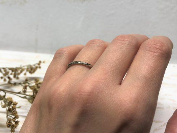 Weißer Verlobungsring mit Hammerschlag getragen an einer Damenhand.