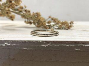 Matter weißer Verlobungsring mit Hammerschlag, dekoriert auf Holz.