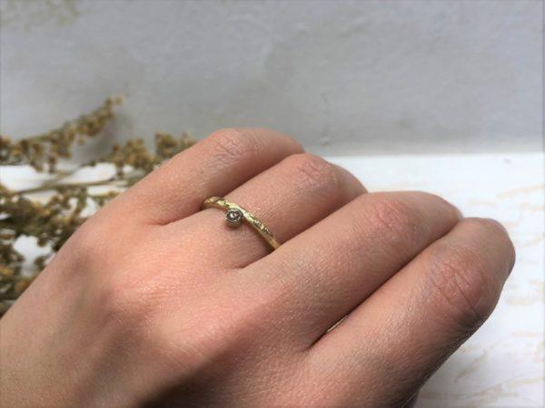 gelber Verlobungsring an der Hand mit glatter Fassung und Stein Beris