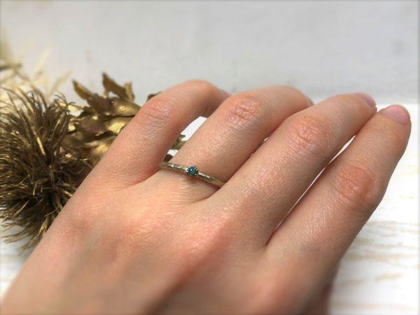 Verlobungsring mit blauem Stein, getragen an einer Hand.