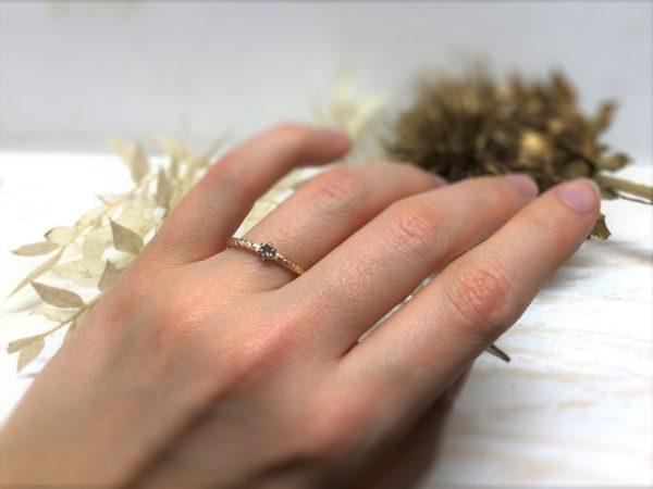 Das Verlobungsringmodell Purpurena an der Hand.