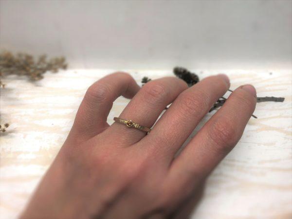 Goldener Verlobungsring mit orange farbenem Stein an der Hand