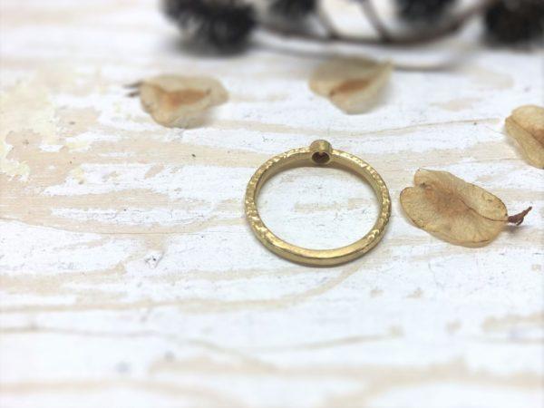 Goldener Verlobungsring mit rotem Stein in glatter Fassung