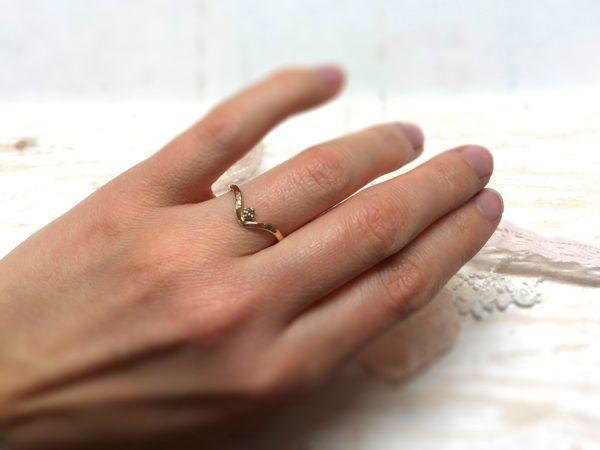 Ein geschwungener Verlobungsring, Modell Rhini, getragen an einer Frauenhand.