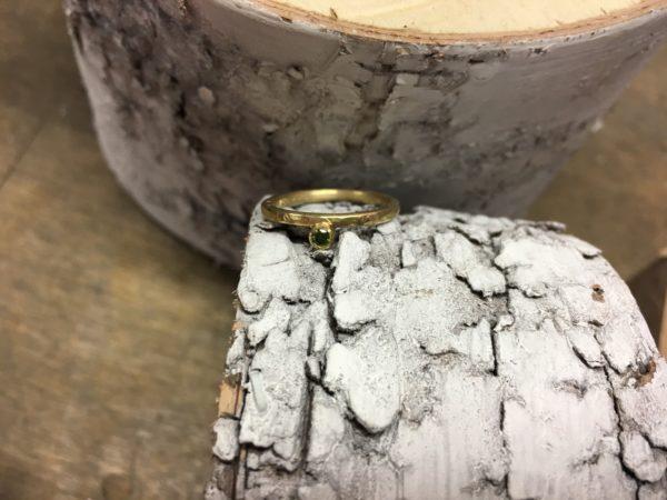 Verlobungsring mit grünem Stein in Gold und Hammerschlag