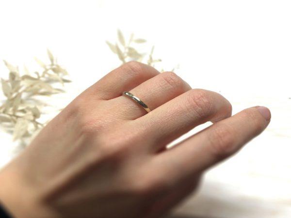 Weißer, gehämmerter Verlobungsring an der Hand