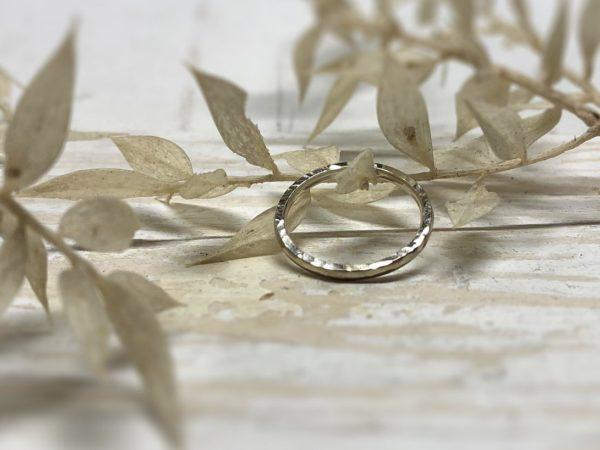 Weißer Verlobungsring mit Hammerschlag auf Pflanzen dekoriert
